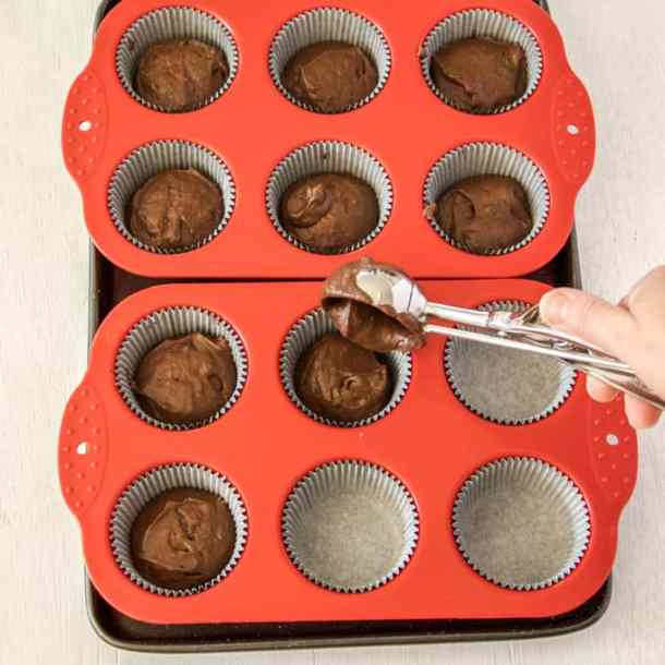 Portioning out chocolate cupcake batter into liners using a medium ice cream scoop