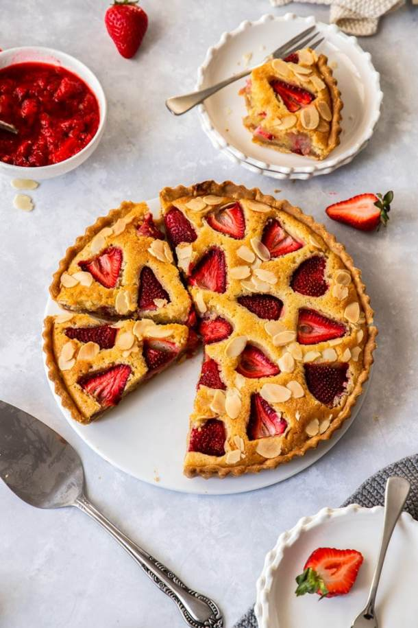birdseye view of a strawberry tart on a white plate. A cake slice sits in front and dessert plates are set around it