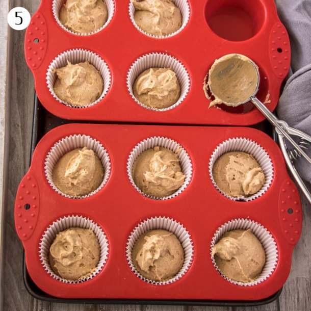 Cinnamon cupcake batter portioned out into cupcake cases in a muffin tin
