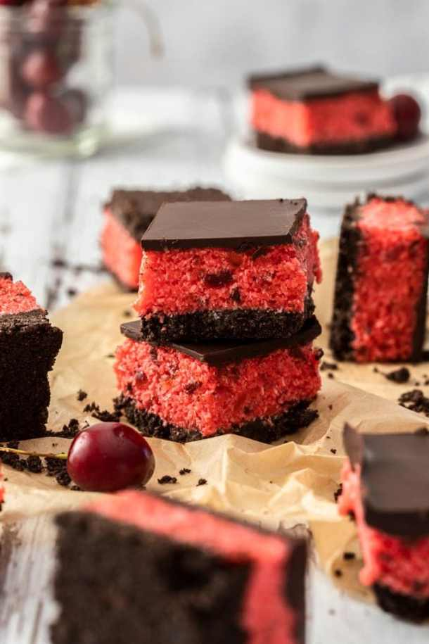 2 pieces of cherry ripe slice stacked, on a piece of brown parchment paper, surrounded by more pieces and fresh cherries