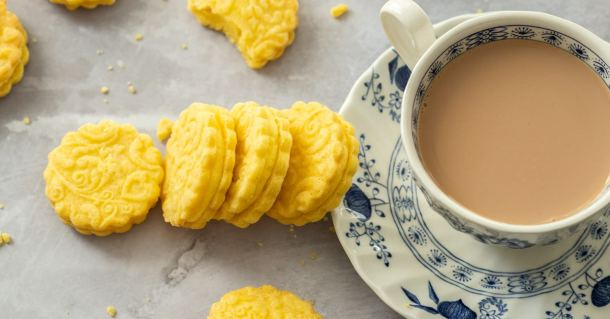4 custard cream biscuits leaning up against a saucer. A cup of tea on top is filled with tea.