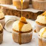 An apple pie cupcake being drizzled with maple syrup, surrounded by more cupcakes and apple slices, on a white background