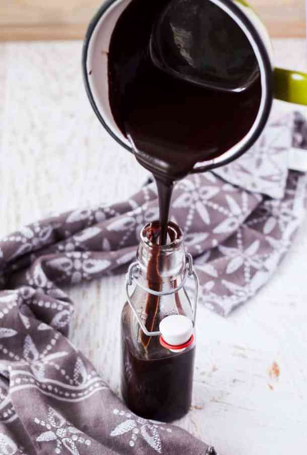 Hot Chocolate Fudge Sauce being poured into a glass bottle
