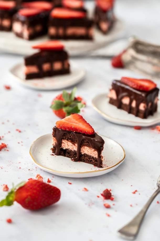 Chocolate petit fours sitting on mini white plates with strawberries surrounding them