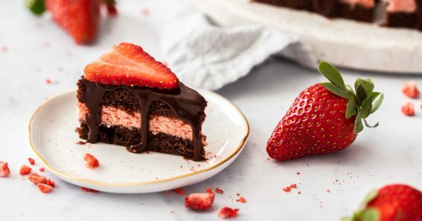 A closeup of a chocolate petit four sitting next to a strawberry