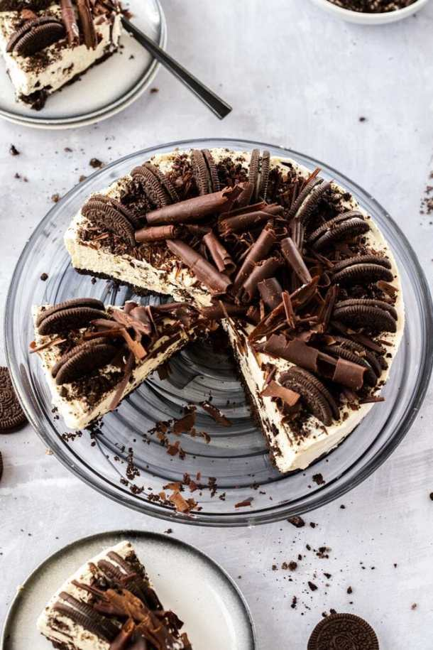 Birdseye view of an oreo cheesecake with a few slices cut out. it sits on a black plate on a concrete table. There are two small plates with slices on next to it