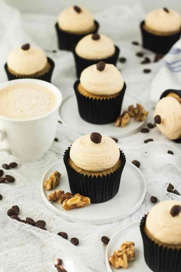 A group of Walnut Coffee Cupcakes surrounded by coffee beans and a cup of coffee