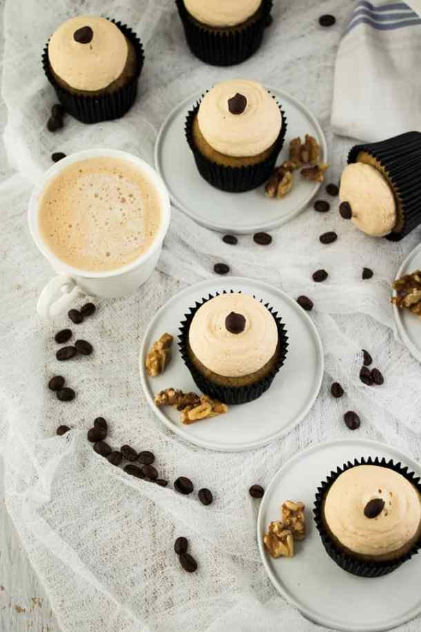 A birdseye view of 6 Walnut Coffee Cupcakes with a cup of coffee