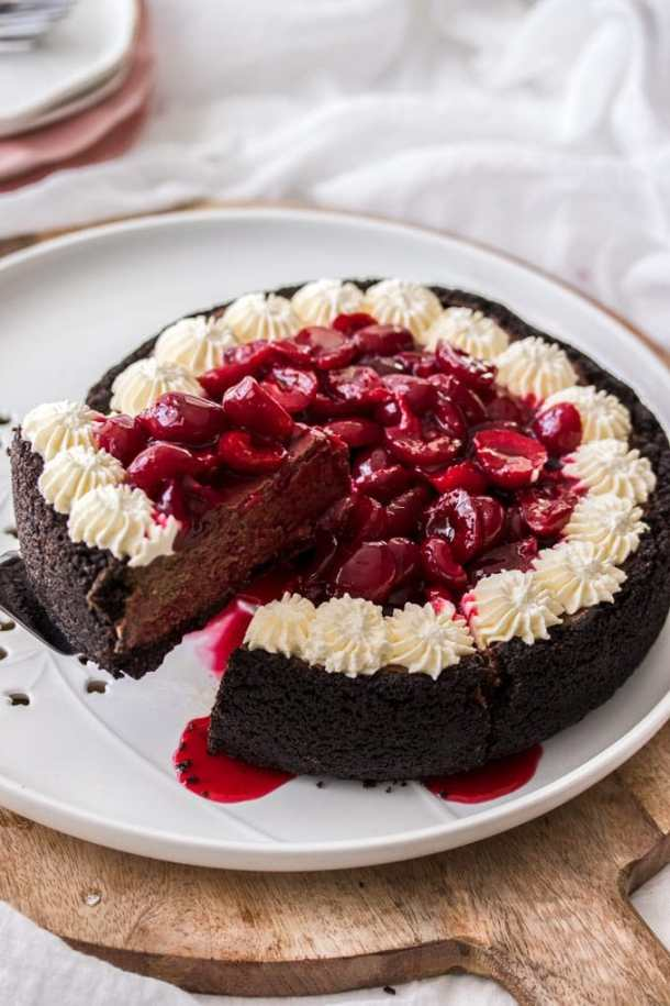 A chocolate cheesecake topped with cherry sauce and cream on a white plate and wooden board
