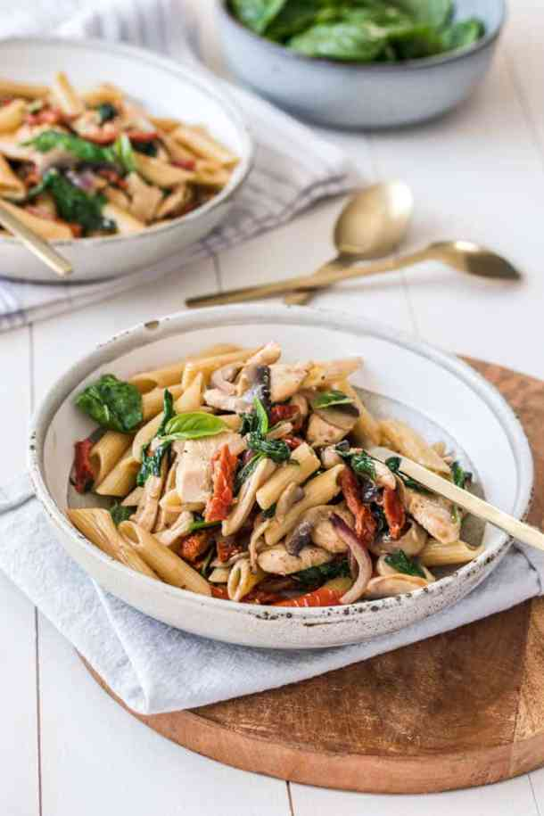 Dishes of Chicken Penne Pasta with sundried tomatoes on a white table top