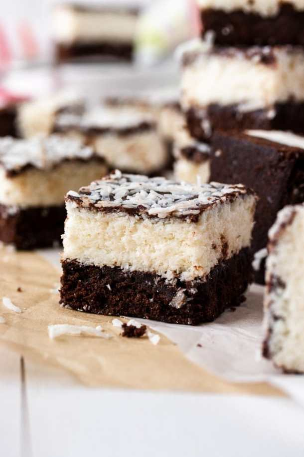 A closeup of one coconut brownie with others blurred in the background