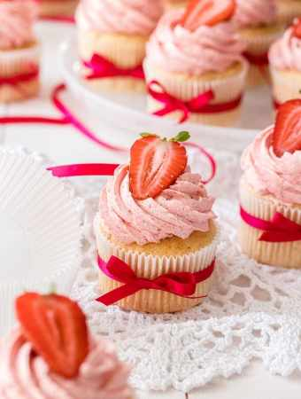 Six Vanilla cupcakes with strawberry buttercream with strawberries on top.