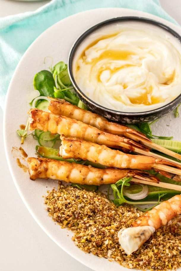 Prawns on a bed of salad with a bowl of yoghurt.