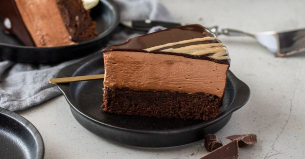 A closeup of chocolate mousse mud cake with spoon in the background