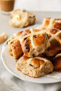 A white plate filled with hot cross buns