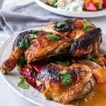 A closeup of roasted harissa chicken on a white plate