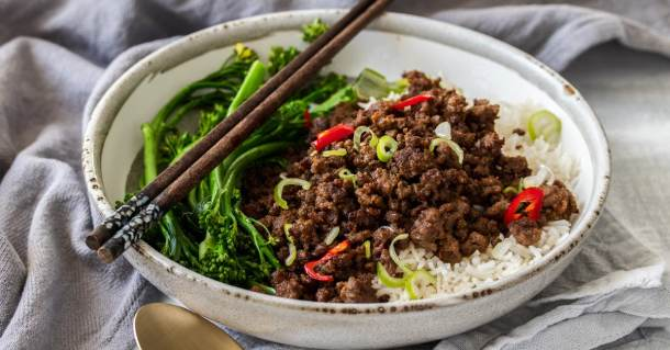 A grey bowl filled with rice, chilli beef mince and broccolini with chopsticks lying across the top