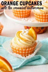 A closeup of an orange cupcake sitting on an aqua tea towel