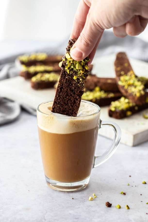 A piece of chocolate biscotti being dunked into a glass cup of coffee