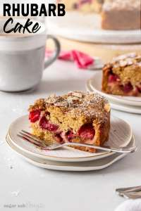 A slice of rhubarb cake sitting on a white plate with a fork next to it