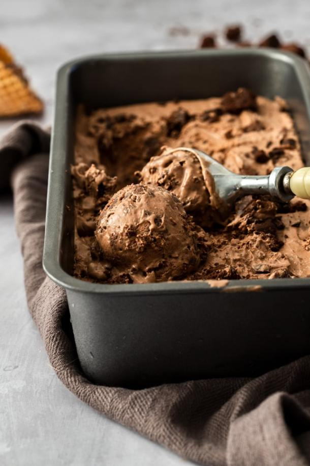 A loaf tin fill with chocolate brownie icec ream with a scoop in it