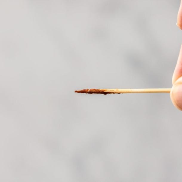 A toothpick showing underbaked brownie batter