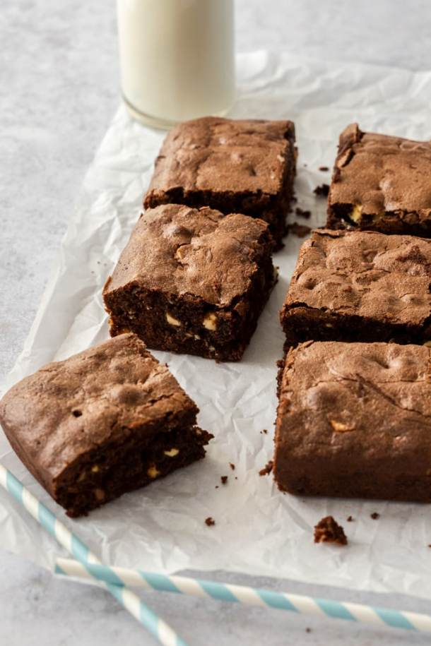 6 brownies sitting on a sheet of baking paper with a jug of milk in the background