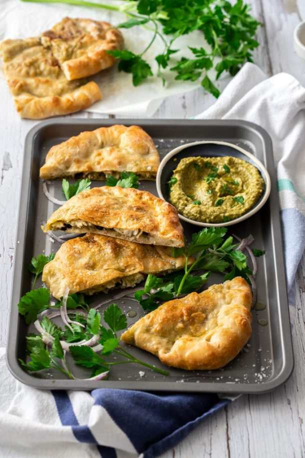 Pesto chicken calzone slices on a grey baking tray surrounded by parsley and onion