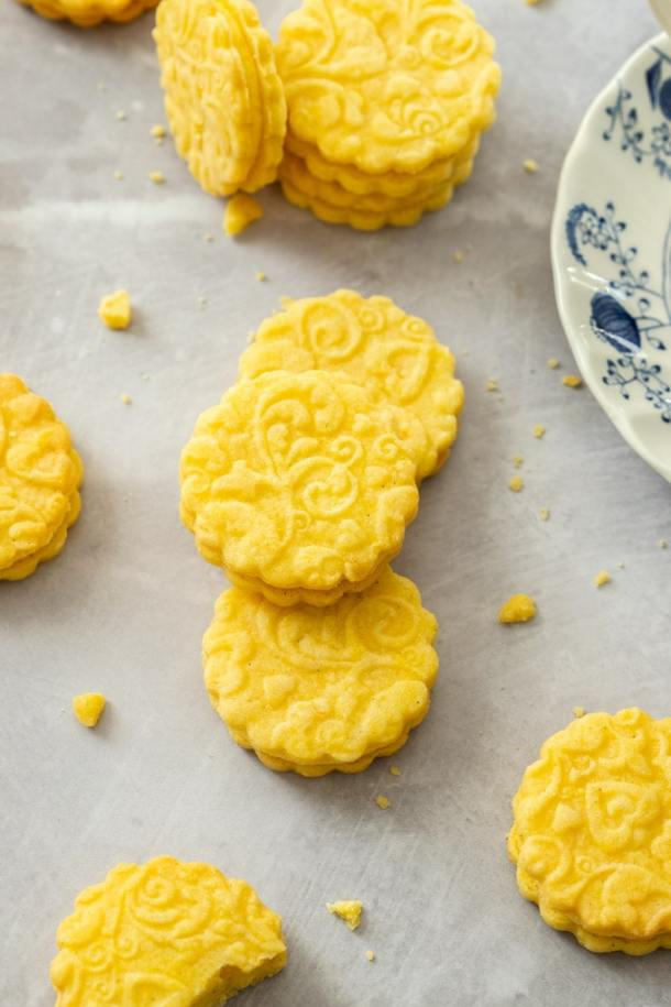 3 stacked custard cream cookies on a grey surface with some others around them
