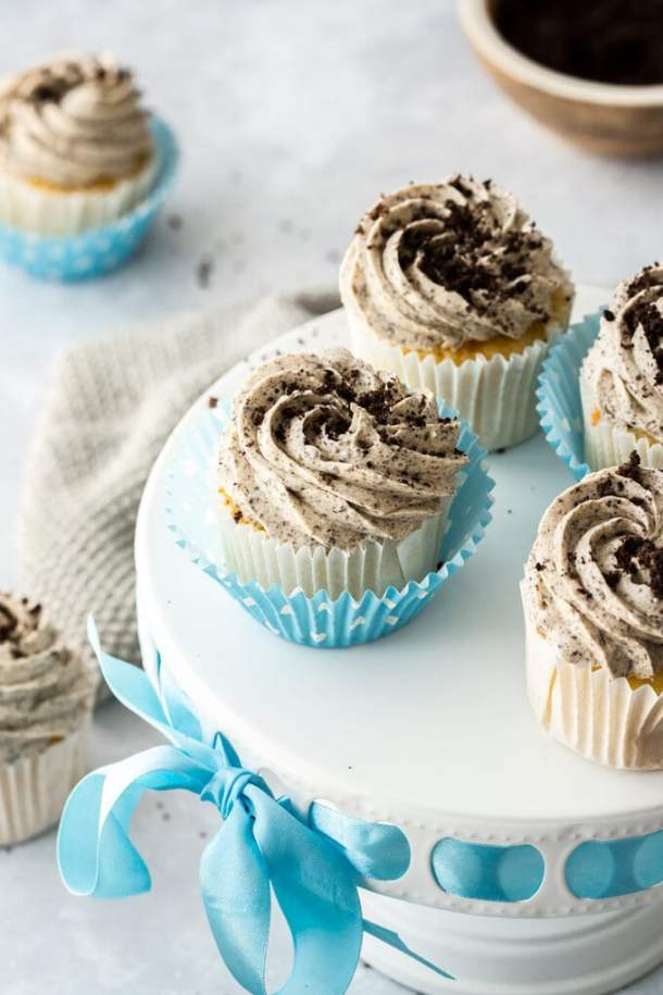 4 cupcakes sitting on a white cake stand, with blue ribbon running around the edge