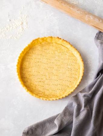 Birdseye view of a pastry tart shell on a floured worktop with a grey tea towel and rolling pin nearby.