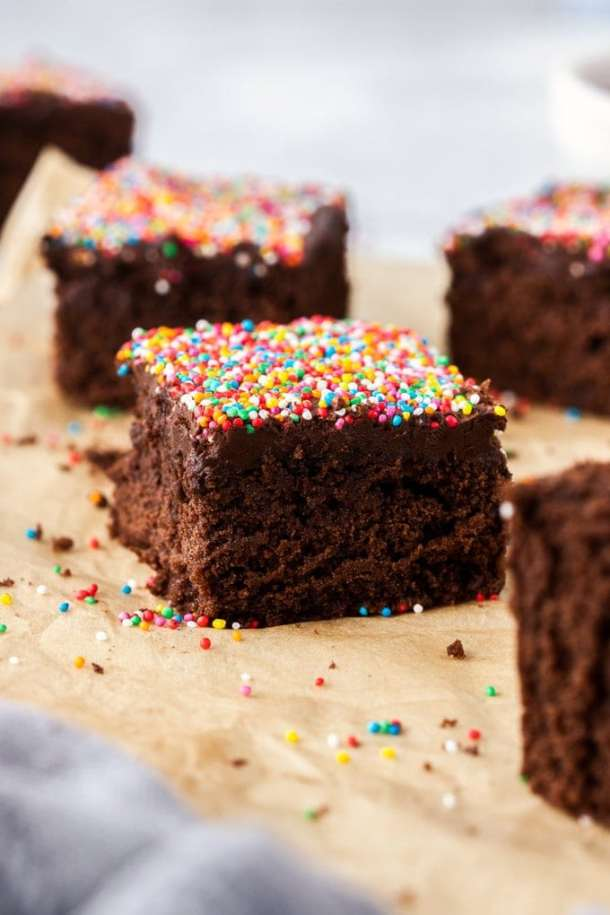 closeup of a piece of chocolate cake topped with sprinkles on a piece of brown parchment paper