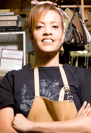 An image of the author in her workshop, wearing an apron, standing beside a chair being refinished.