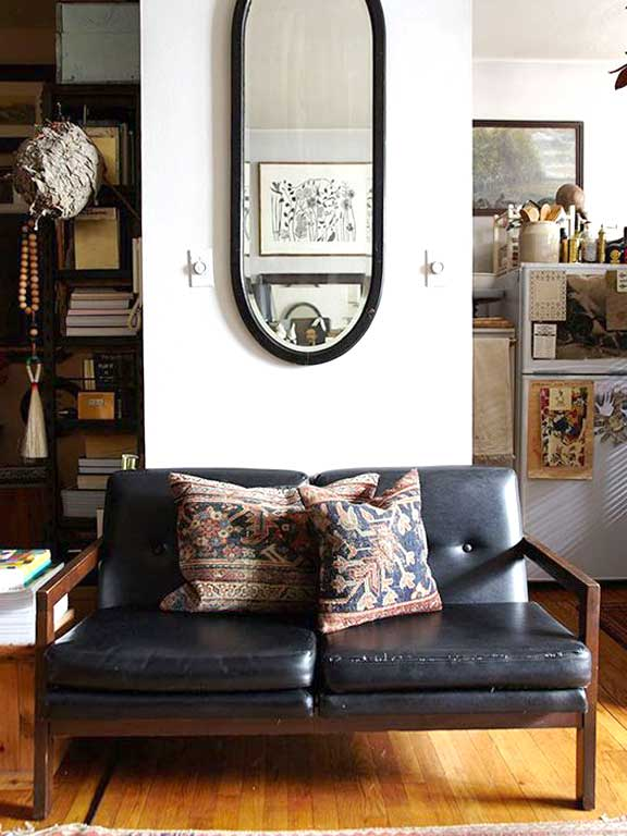 A mid-century modern love seat against a wall