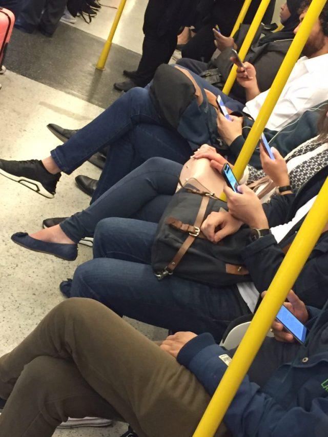Persone con smartphone nella London Underground