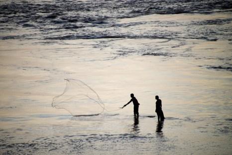 Two local fishermen fishing at dusk in Tabatinga, Amazon rainforest, Colombia