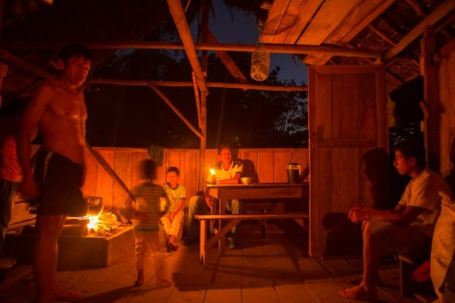 Family and friends visiting by candlelight in Santa Barbara, a remote cacao harvesting community along Rio Arajuno, Ecuador