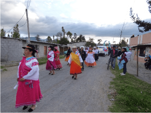 During the carnival parade in La Calera, with the band playing and people singing and dancing, near Otavalo in Ecuador
