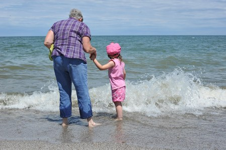 A grandmother and grandchild explore the power of Lake Erie on a summer day at Geneva State Park's beach. The lake's waves, during times of high lake levels, under cut the bluffs along the shoreline and eventually claim the land.