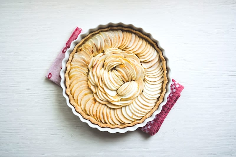 Round dish of apple pie on red tea towel on white background.