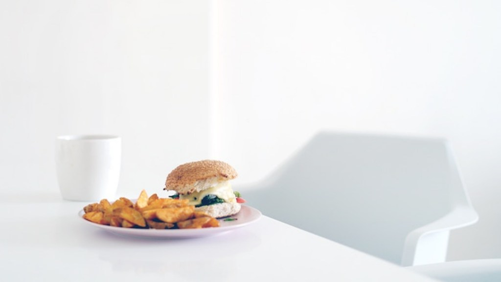 Vegan burger and sweet potato fries on white table in white room with white chair.