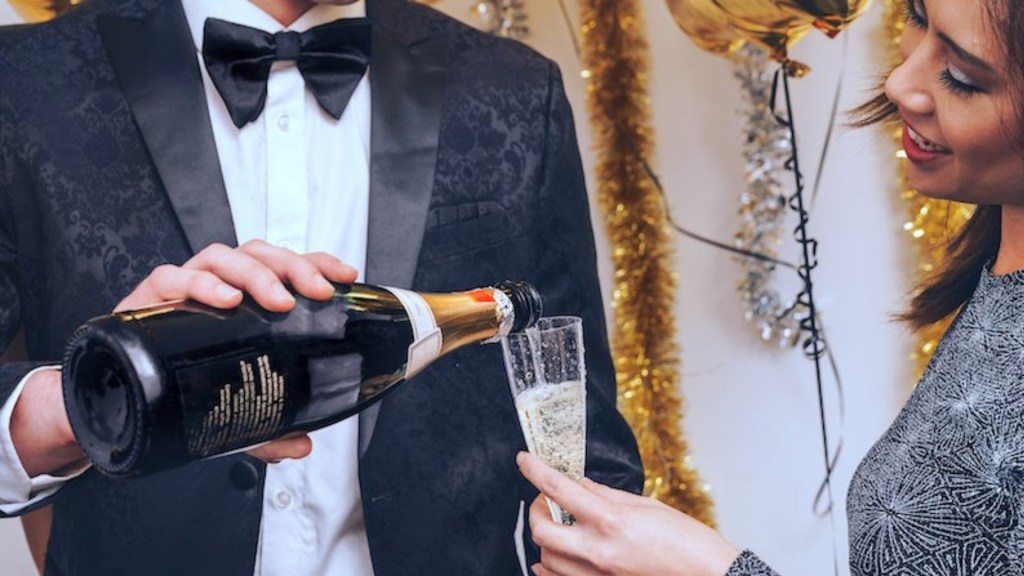 Man in tuxedo pouring a glass of Champagne for woman in fancy dress.