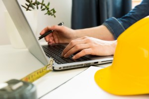 Contractor working on a computer with measuring tape and construction hat.