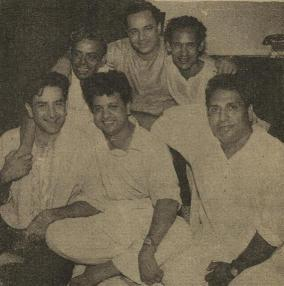 Mukesh with arms around Shailendra on one side and Hasrat Jaipuri on the other. In the front row are Raj Kapoor, Jaikishan and Shankar