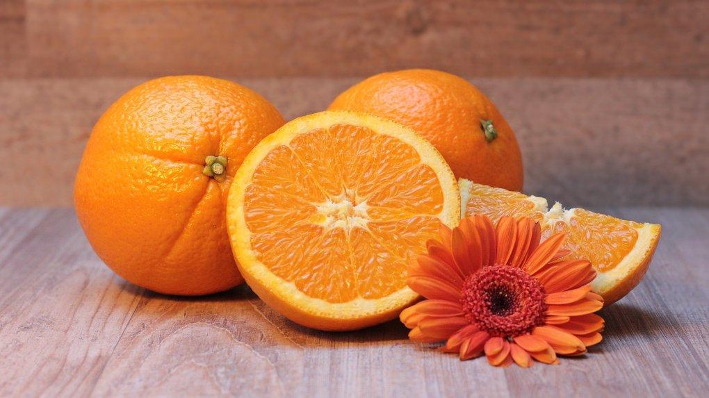 Imagem mostra laranjas em destaque junto a uma flor.