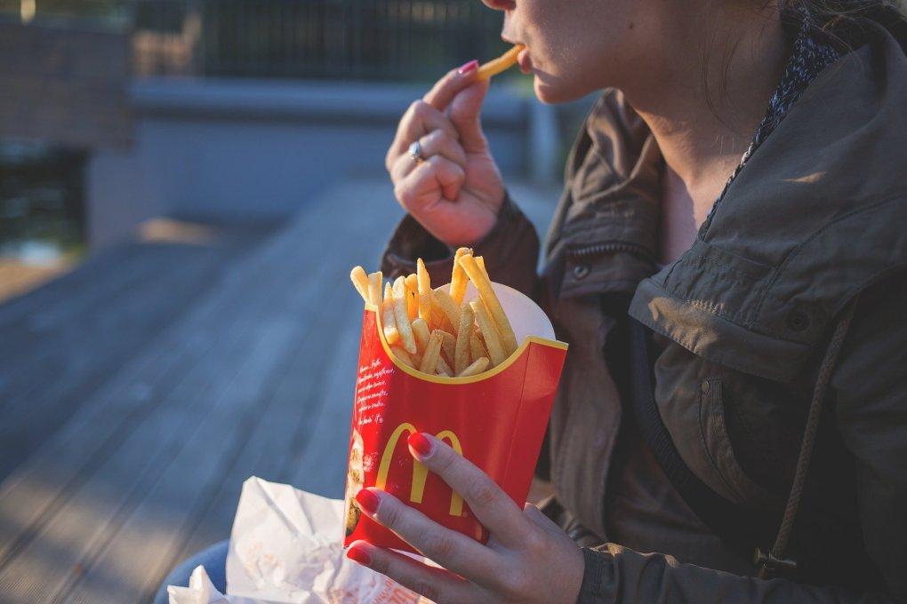 Mulher comendo batata frita de rede fast food.