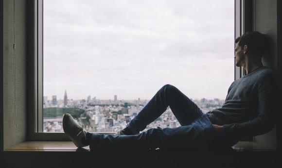 Homem sentado na janela.