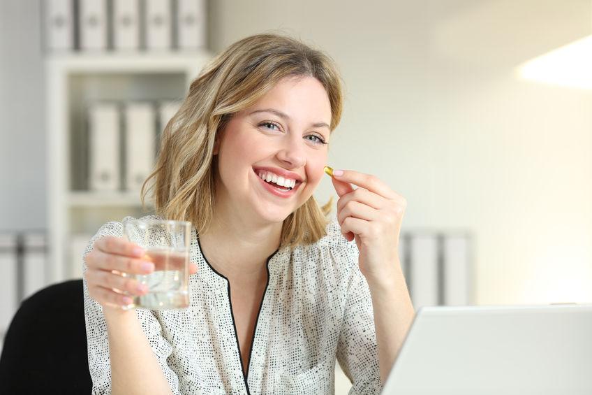 Imagem de uma mulher tomando um suplemento.