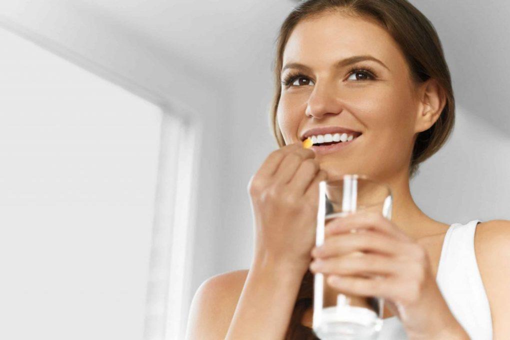Mulher tomando cápsula com corpo de água.