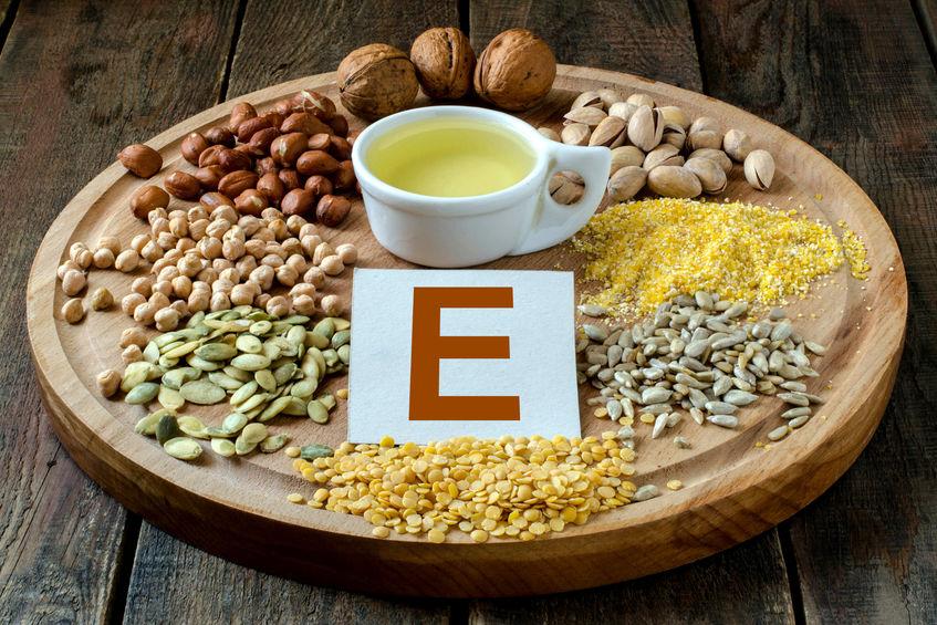 """Semente e óleo vegetal em cima de uma tábua de madeira, com a letra """"E"""" no centro."""